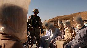 Ein US-Soldat 2003 mit Gefangenen im Irak.