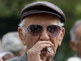 Ein griechischer Rentner raucht während einer Demonstration gegen Sparmaßnahmen der Regierung in Athen.