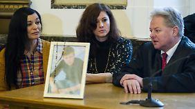 Die Mutter des Opfers, eine Bekannte (l.) und Rechtsanwalt Michael Jäger sitzen im Landgericht hinter einem Bild des getöteten Sohnes.