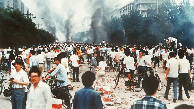 Rauchsäulen, Verwüstung und ratlose Menschen auf der Chang'an Avenue in Peking am 4. Juni 1989. Die Straße führt unmittelbar am Platz des Himmlischen Friedens vorbei.