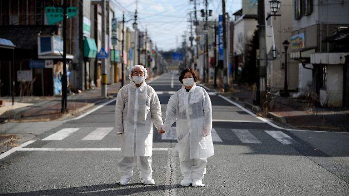 Die Stadt Namie in der Präfektur Fukushima ist weiterhin leer, die Einwohner dürfen nur für wenige Stunden zurückkehren. Sie tragen dann Schutzkleidung - wie dieses Ehepaar.