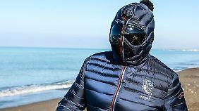 Grillo mit einem Ganzkörperanzug am winterlichen Strand von Marina di Bibbona.