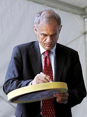 Der zyprische Finanzminister Michalis Sarris unterzeichnet zur Euro-Einführung symbolisch eine große Münze.