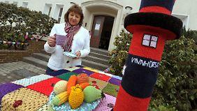 Petra Schulz präsentiert ihr bestricktes Kaffeegeschirr zusammen mit bestrickten Steinpfeilern, Gemüse und einem Leuchtturm.