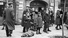 450.000 Menschen lebten 1941 im Warschauer Ghetto unter unmenschlichen Bedingungen. Unklar ist, ob das auf dem Gehsteig liegende Kind auf dem Foto tot oder lebendig ist.