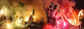 Fans von Hannover 96 zünden bengalische Feuer.