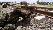 Syrische Regierungssoldaten sichern nahe Damaskus eine Bahnstrecke.