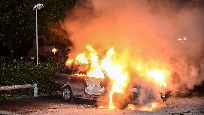 Feuerwehrleute löschen ein brennendes Auto. Auch in der Nacht zu Samstag brannten wieder Fahrzeuge. (Archivbild).
