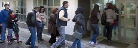 Menschen stehen vor einem Arbeitsamt im südspanischen Sevilla Schlange.