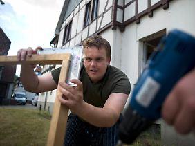 """Steffen konstruiert einen Holzrahmen für das sanierungsbedürftige """"Streetworker Haus"""" in Sehnde auf dem Klinikumgelände Wahrendorf."""