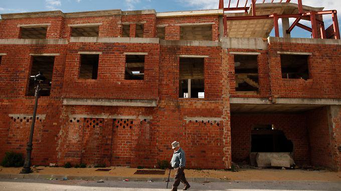 Im südspanischen Cancelada geht ein Mann an unfertigen Häusern vorbei.