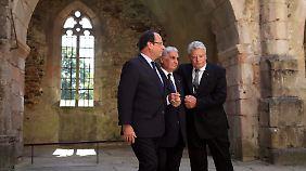 Hollande und Gauck stützen Hébras in der Ruine der ausgebrannten Kirche von Oradour.