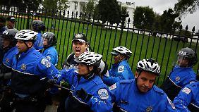 Polizisten drängen vor dem Weißen Haus wütende Demonstranten zurück.