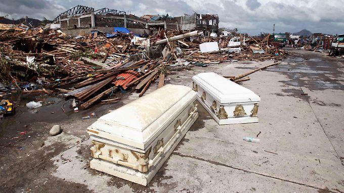 Tod und Verwüstung: In der Stadt Tacloban liegen leere Särge, die vermutlich aus einem Bestattungsunternehmen herausgespült wurden, auf der Straße.