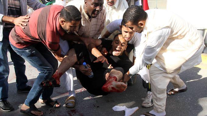 Helfer kümmern sich um einen verletzten Demonstranten.