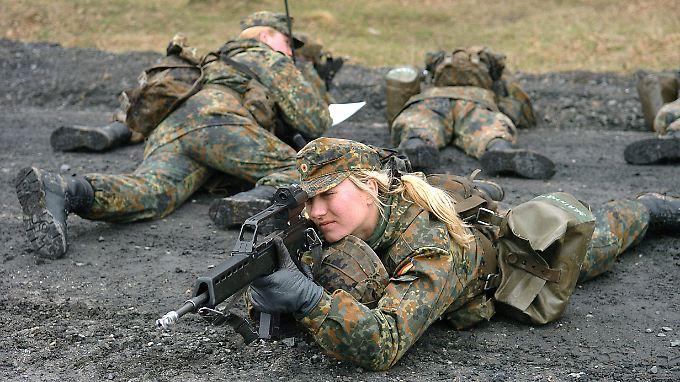 Eine Rekrutin sichert auf einem Truppenübungsplatz eine Patrouille.