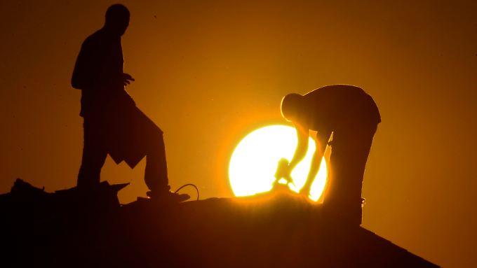 Männer auf einem Hausdach: Begrünung oder Reflektoren auf Dächern sollen der Erderwärmung entgegenwirken können.