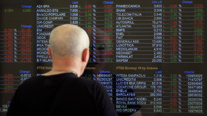 An der Mailander Börse schaut ein Mann auf die Kurstafel.
