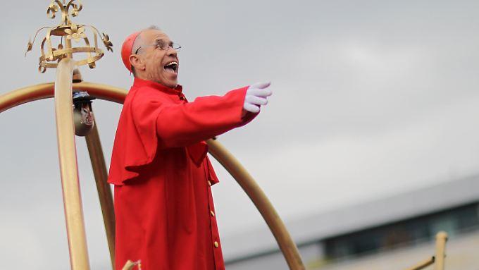 Ein als Bischof Franz-Peter Tebartz-van Elst verkleideter Narr feiert beim Rosenmontagszug in der Innenstadt von Mainz (Rheinland-Pfalz) und jubelt den Menschen von einer goldenen Kanzel aus zu.