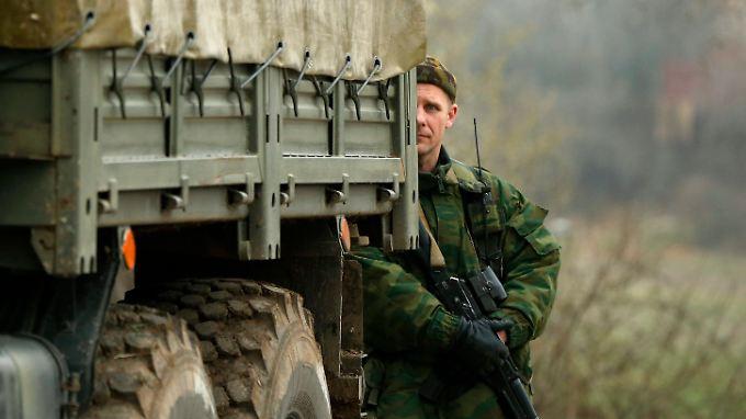 Ein uniformierter Mann, vermutlich ein Russe, steht hinter einem Laster in Sewastopol.