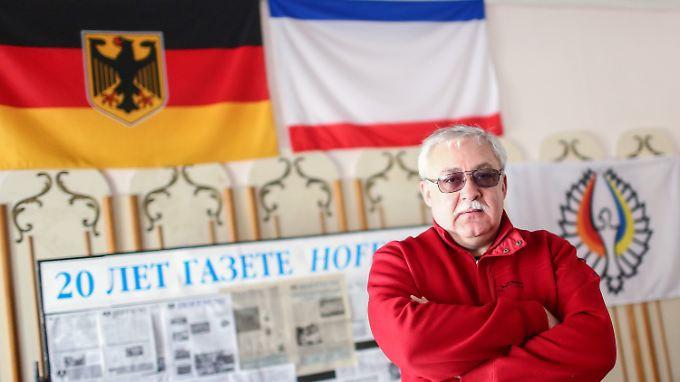 Juri Gempel posiert in seinem Büro vor der deutschen und der Krim-Flagge.
