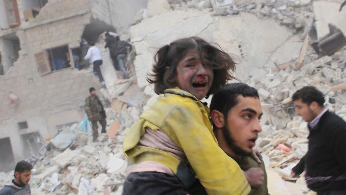 Bombenangriff in Aleppo. Ein junger Mann hat ein Mädchen aus den Trümmern gerettet.