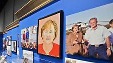 Mit dabei: Angela Merkel. Das Bild zeigt die deutsche Kanzlerin, wie sie freundlich dreinblickt. Sogar ein angedeutetes Lächeln ist erkennbar. Auch die hellen, warmen Farben lassen Merkel sympathisch erscheinen.