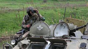 Ein ukrainischer Soldat beobachtet die Lage an einer Straßensperre bei Slawjansk.