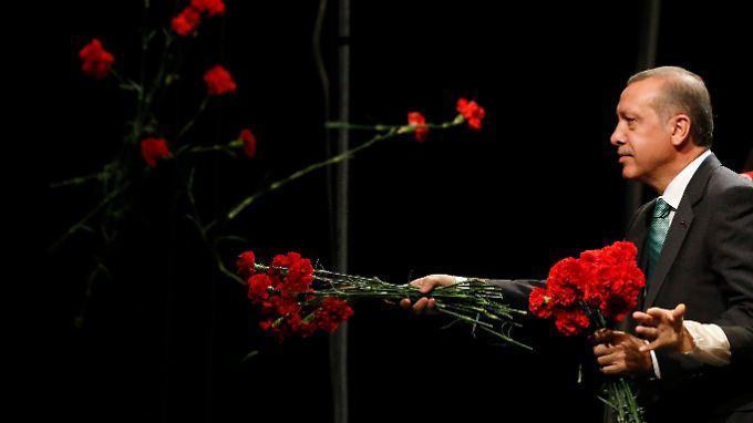 Erdogan wirft rote Blumen ins Publikum. Auch ohne Blumen hätte der türkische Premier seine Fans begeistert.