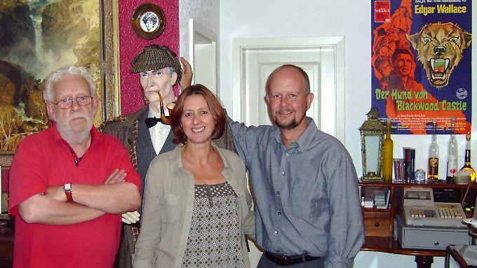 Krimiautor Ralf Kramp (r), seine Frau Monika und der Schriftsteller Jacques Berndorf im Café Sherlock des Kriminalhauses von Hillesheim. In der Bibliothek des Hauses stehen rund 26.000 Kriminalfälle im Bücherregal.