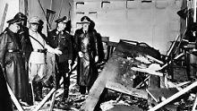 Hermann Göring (helle Uniform) Hitlers Kanzleichef Martin Bormann (links) begutachten den zerstörten Raum der Kartenbaracke.