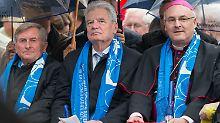 Gauck sitzt während der Eröffnungsfeier des Katholikentags neben dem ZdK-Präsidenten Alois Glück (l) und dem Regensburger Bischof Rudolf Voderholzer.