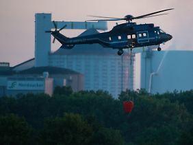 Einsatz bis in die späten Abendstunden: Ein Hubschrauber der Bundespolizei befüllt einen Wasserbehälter im Elbe-Seitenkanal, um ihn wenig später über einen brennenden Silo zu entleeren.
