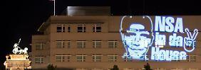 """Der Schriftzug """"NSA in da House"""" und das stilisierte Victory-Zeichen waren in der Nacht zum 19.07.2014 in Berlin auf die Fassade der US-Botschaft projiziert worden."""