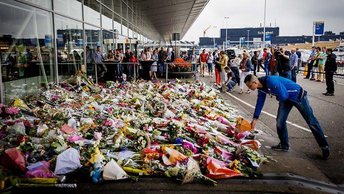 Am Amsterdamer Flughafen legt ein Mann Blumen nieder. Dort war das Flugzeug gestartet.