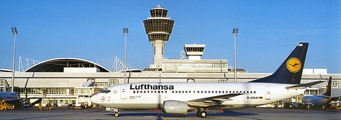 Am Boden: Eine Boeing 737 der Lufthansa vor dem Tower des Münchner Flughafens (Archivbild).