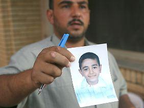 Mohammed Hafiz zeigt ein seines zehnjährigen Sohnes Ali, der bei dem Angriff auf die Menschenmenge auf dem Nussir-Platz ums Leben kam.