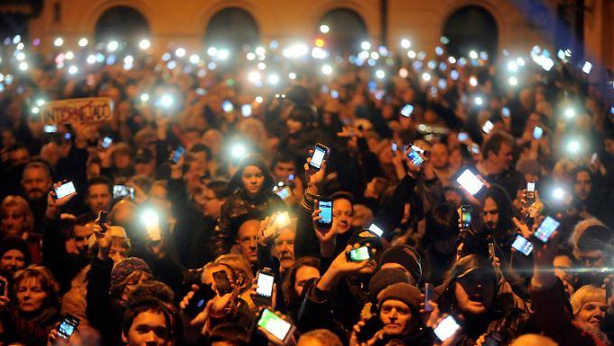 Mit hell erleuchteten Smartphones tun mehr als zehntausend Ungarn in Budapest ihre Meinung kund.