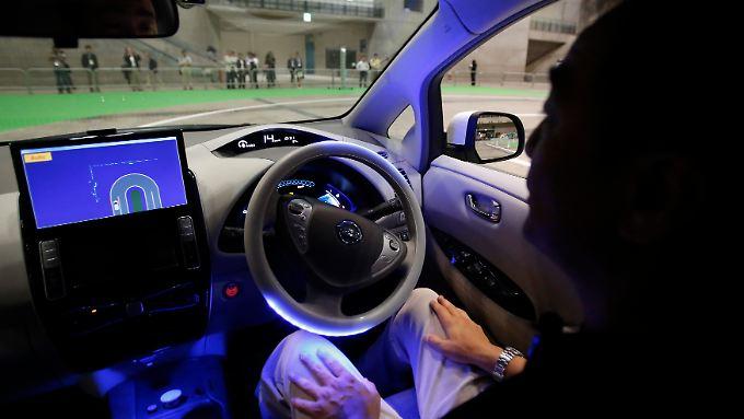 Ein Nissan-Mitarbeiter hinter dem Steuer eines autonom fahrenden Autos.