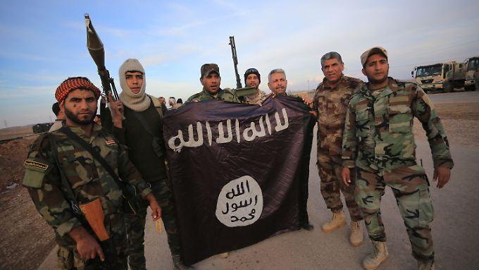 Irakische Soldaten präsentieren eine erbeutete IS-Flagge.
