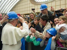Populäre Geste im März 2014: Bei einem Treffen mit Stahlarbeitern und ihren Familien aus Terni setzt Papst Franziskus einen Schutzhelm auf.