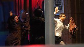 Geiseln flüchten kurz vor der Stürmung aus dem Café und werden von den Sicherheitskräften empfangen.
