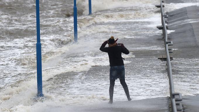Wellen überspülen den Fähranleger in Dagebüll (Schleswig-Holstein), während eine Frau gegen den Wind kämpft.