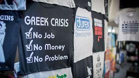 """Zur Not muss Sarkasmus helfen: """"Keine Arbeit, kein Geld, kein Problem"""", heißt es auf diesem T-Shirt in einem Geschäft in Athen."""