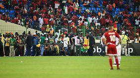 Flucht in den Innenraum: Ghanaische Fans und Pressevertreter versuchten sich den Wurfgeschossen der Heimzuschauer zu entziehen.