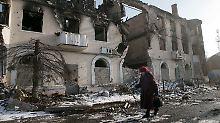 Eine Frau läuft in Vuhlehirsk an einem zerstörten Gebäude vorbei.