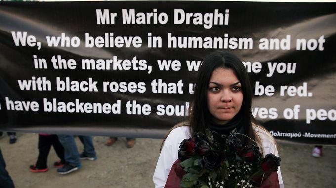 Ein Mädchen demonstriert mit schwarzen Blumen gegen die Sparpolitik der EZB in Nikosia. Im Hintergrund ein Brief an EZB-Chef Draghi.