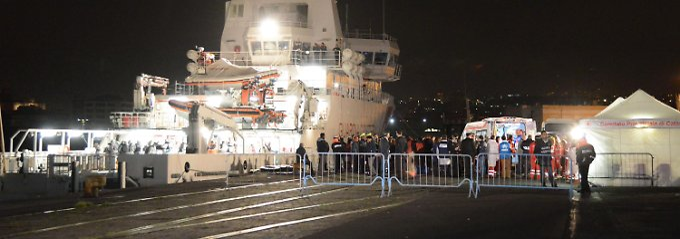 """Gespenstische Szenen im Hafen von Catania: Das Küstenwachschiff """"Bruno Gregoretti"""" liegt festgemacht an der Pier, die Überlebenden der Katastrophe erreichen Europa."""