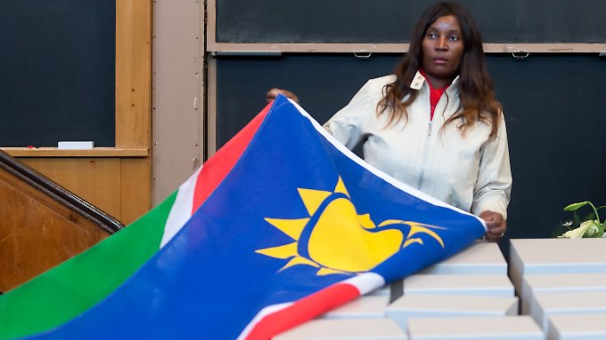 Übergabe von Gebeinen aus Namibia im März 2014. Eine Teilnehmerin der namibischen Staatsdelegation entfernt in der Berliner Charité die namibische Flagge von Behältnissen mit den sterblichen Überresten.