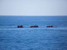 Beiboote der deutschen Fregatte nähern sich einem Schlauchboot: Spätestens wenn das Wetter umschlägt, wären die Flüchtlinge ohne Hilfe verloren gewesen.